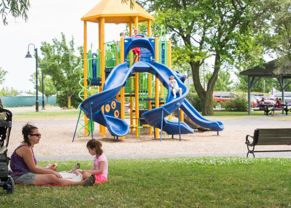 A mother and child sit in front of Kershaw Park's playground