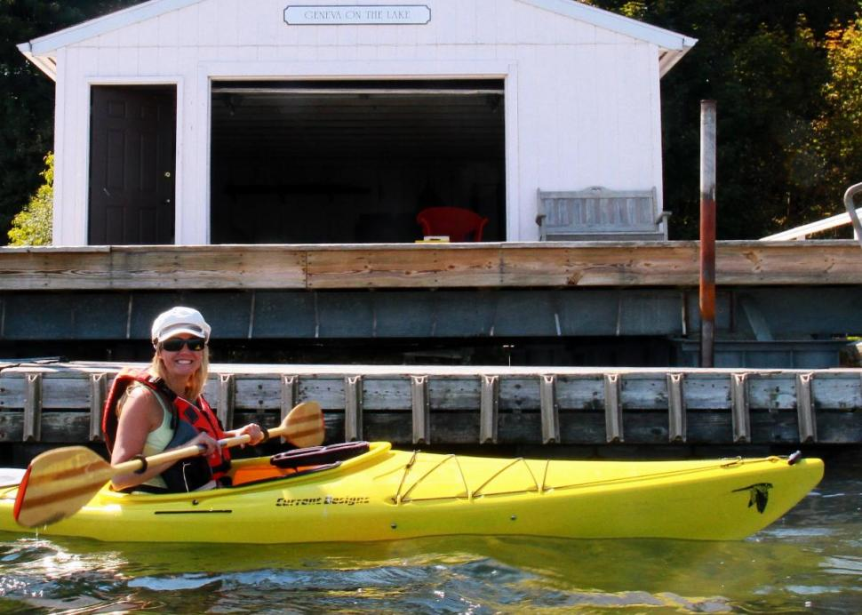 Woman kayaking in front of boathouse