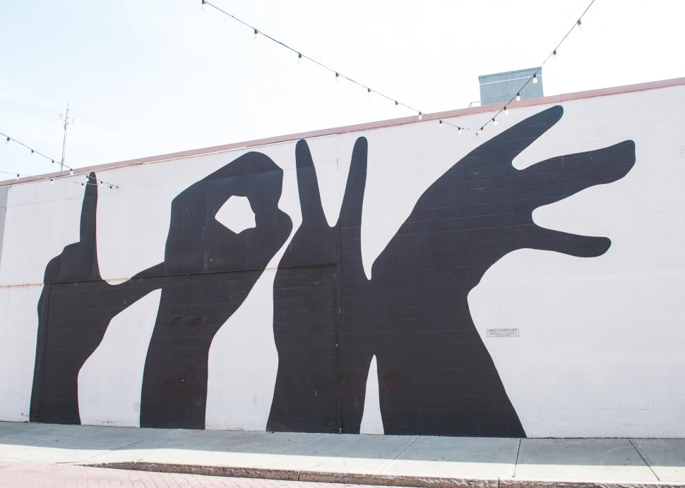 A mural of silhouetted hands painted on a building on Linden Street