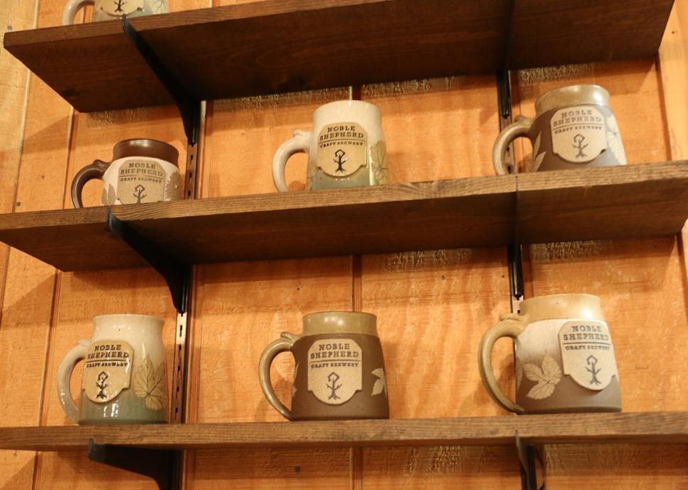 Mugs sit on shelves inside of the Noble Shepherd in Bloomfield