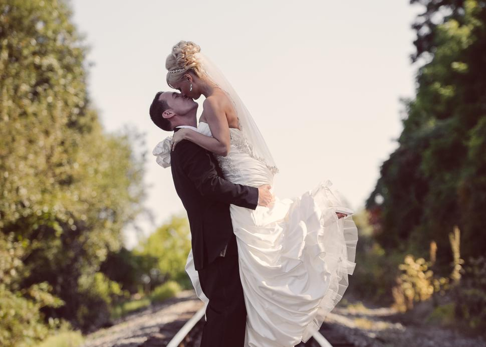 Bride and Groom embracing on railroad tracks that cross near Belhurst Castle