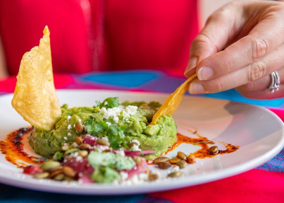 Closeup of a woman dipping a chip into guacamole at Rio Tomatlan in Canandaigua