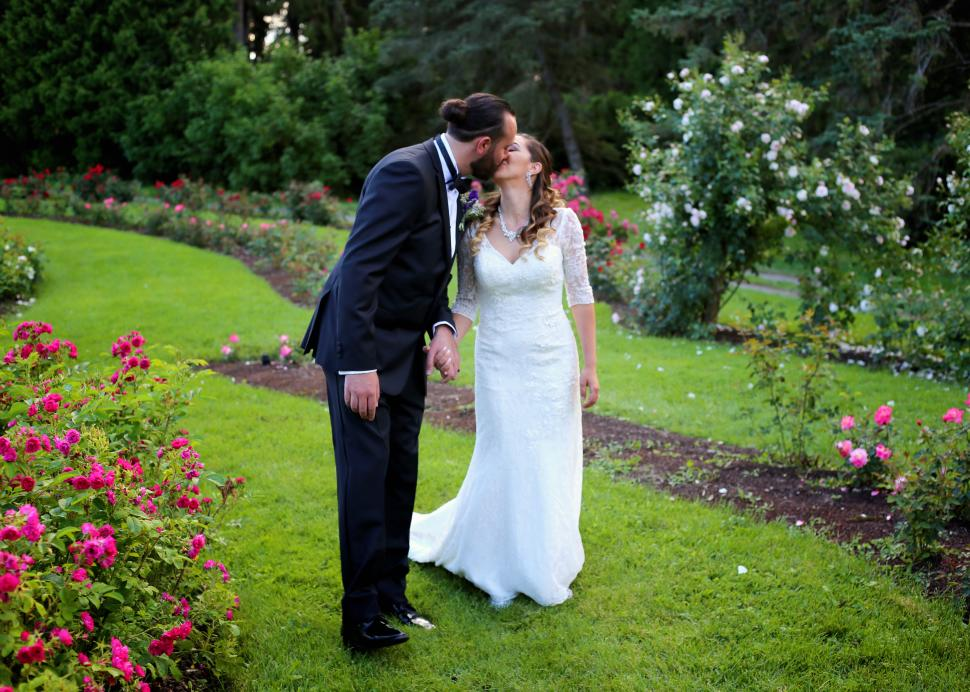 A bride and groom kiss within the gardens at Sonnenberg Mansion