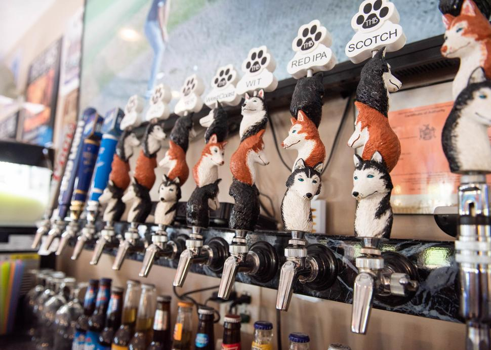 Closeup of taps holding craft brews from Three Huskies Brewing