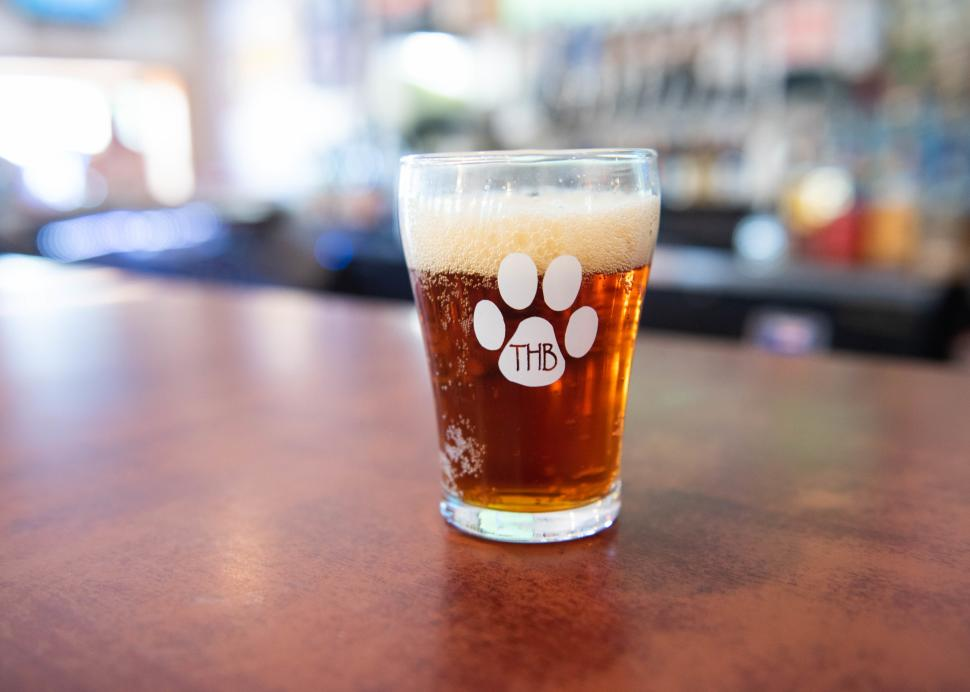 A glass of freshly brewed beer sits on a table inside of Three Huskies Brewing