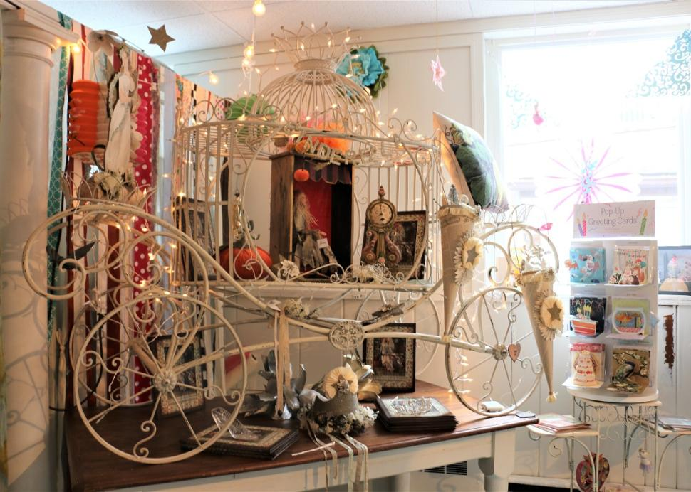 A wire carriage sits on a table inside of True Lily in Canandaigua