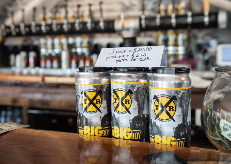 Cans of beer sit on a shelf inside of Twisted Rail Brewing