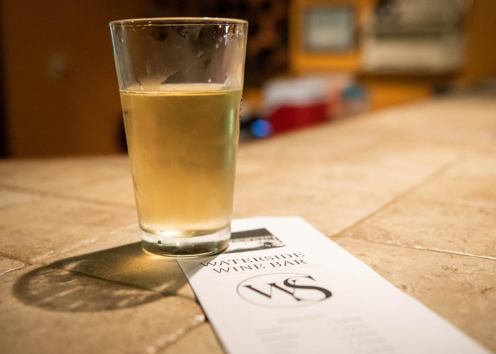 A glass of beer sits on top of the menu at Water Side Wine Bar