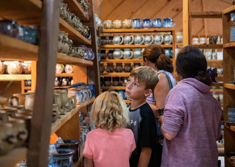 A family check out items inside of the Wizard of Clay pottery in Bloomfield