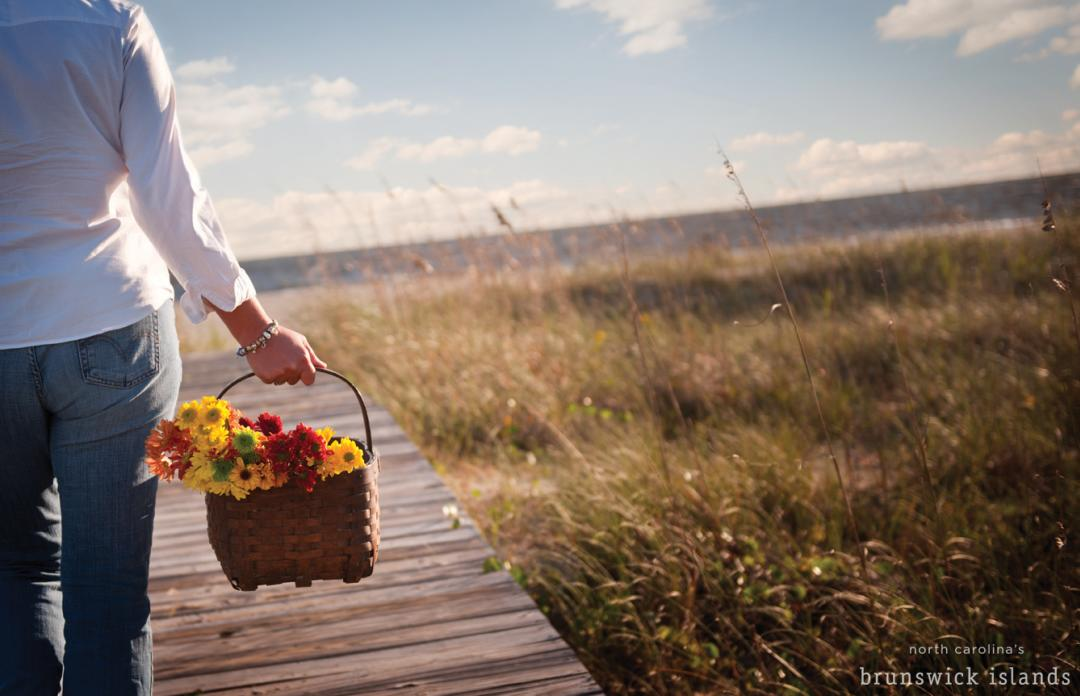 A visitor carries a picnic basket full of fresh cut flowers down a beach boardwalk.