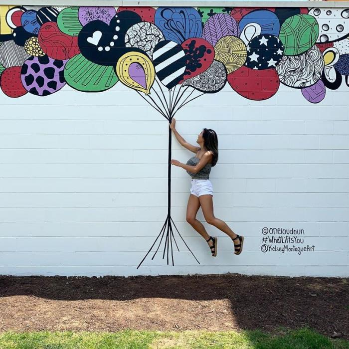 Woman jumping in front of balloons mural at One Loudoun
