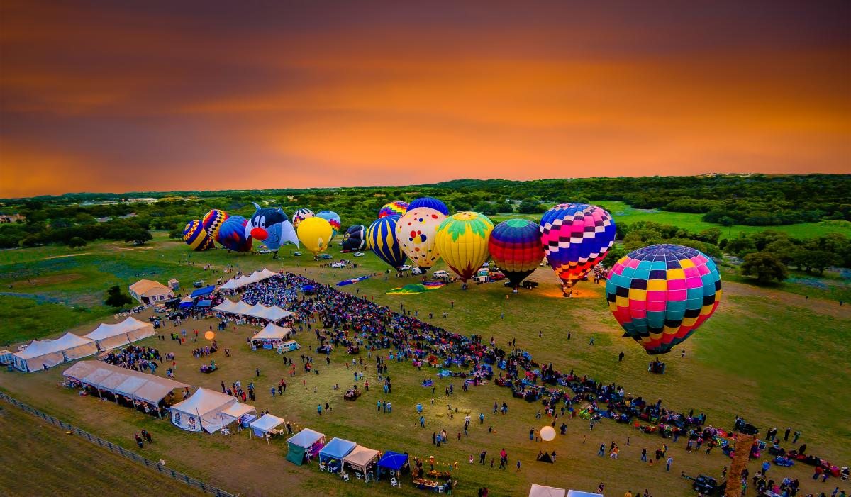 Aerial view of the balloons converging at sunset before taking flight