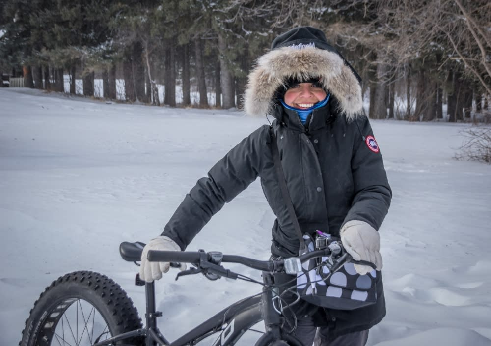 woman in the snow in a parka with a fat tire bike