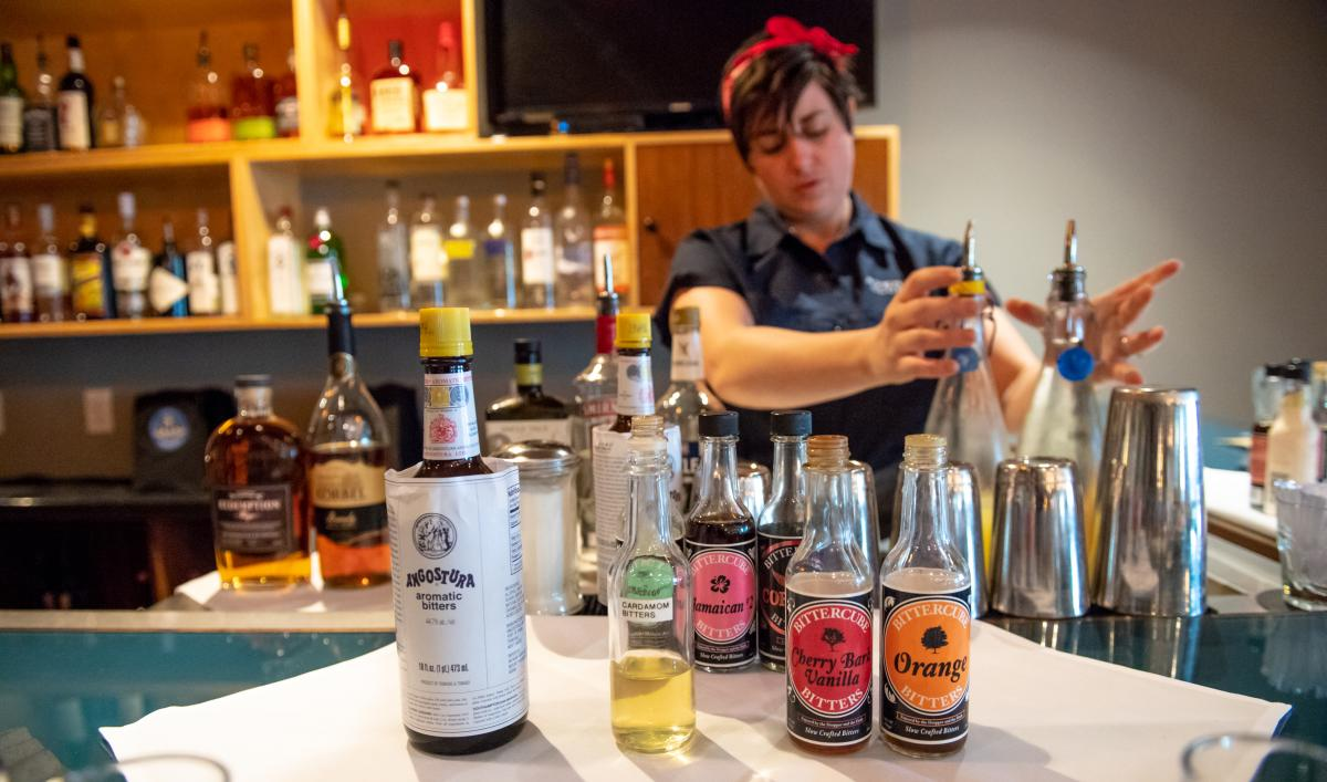 Avenue Club bartender stands behind assortment of bitters