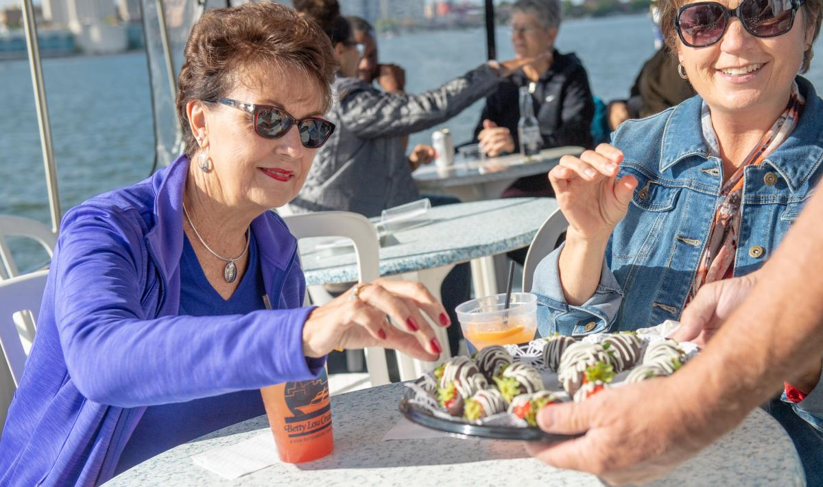 Two women pick from a platter of chocolate covered strawberries during the Betty Lou View of Madison experience