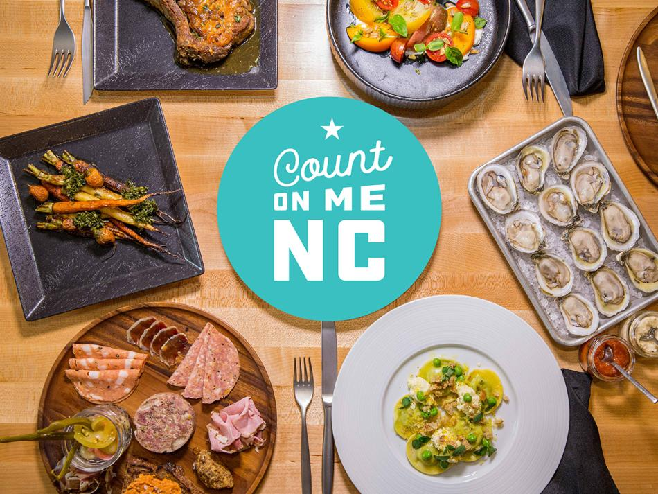 Bright blue Count On Me NC badge icon on a photo of plates of food laid out on a wooden table top.