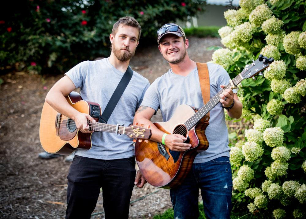 Two guys holding guitars at 868 Estate Vineyards in Loudoun County