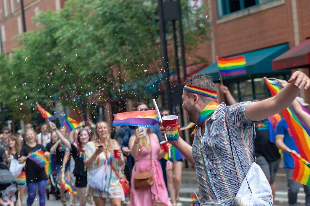 A crowd holding rainbow flags at the Cincinnati Pride Parade