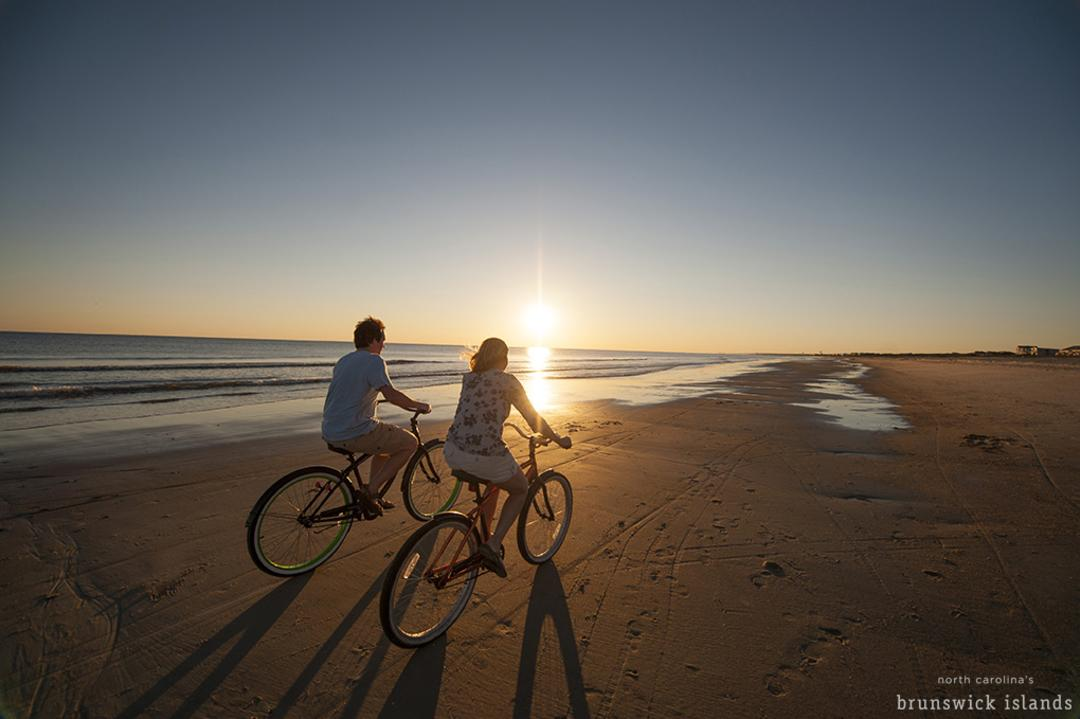 A couple riding bikes on the beach during sunset in the Brunswick Islands