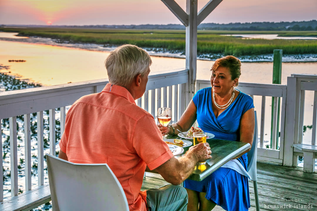 Couple dining on the waterfront at sunset in North Carolina's Brunswick Islands