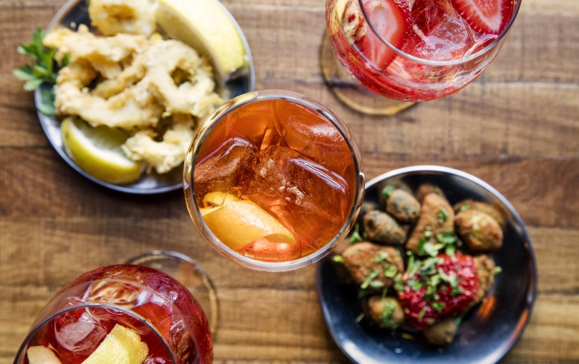 mixed drinks and food on a table.