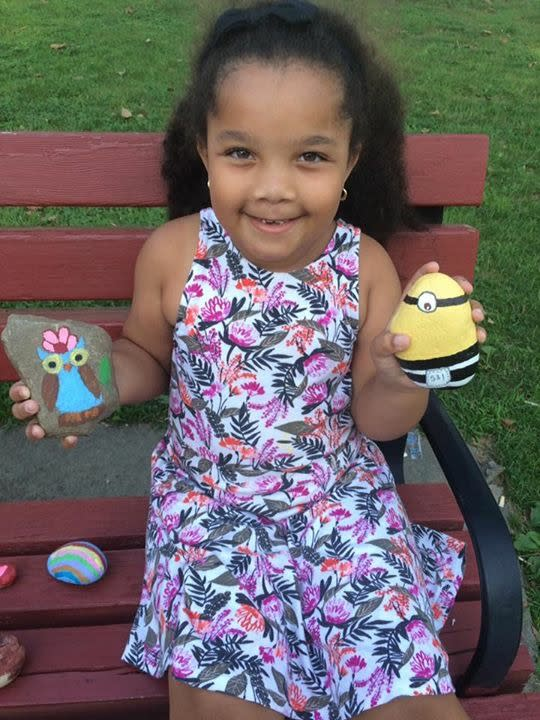 Child with minion and owl painted rocks