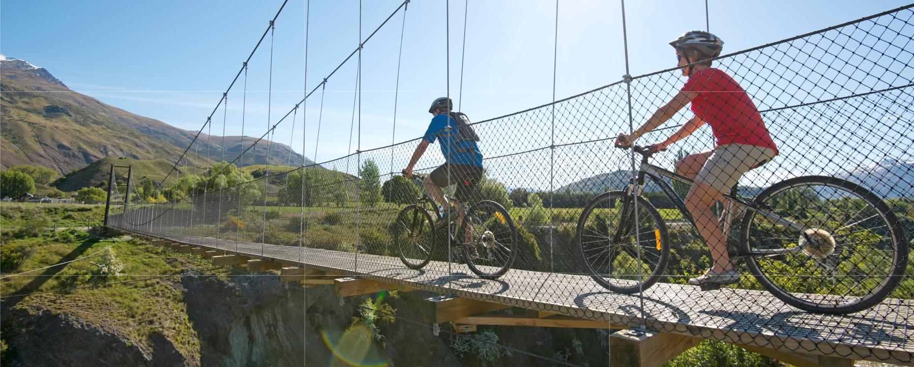 Couple biking over the Edgar Bridge, Gibbston