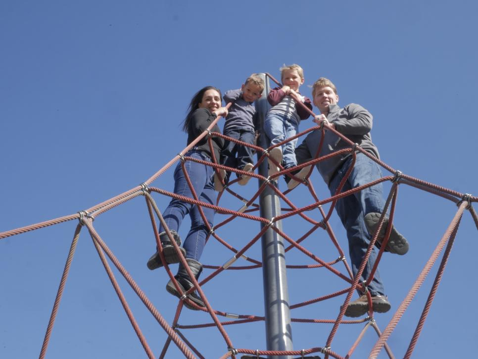 A family atop a playground jungle gym in Carmel, IN