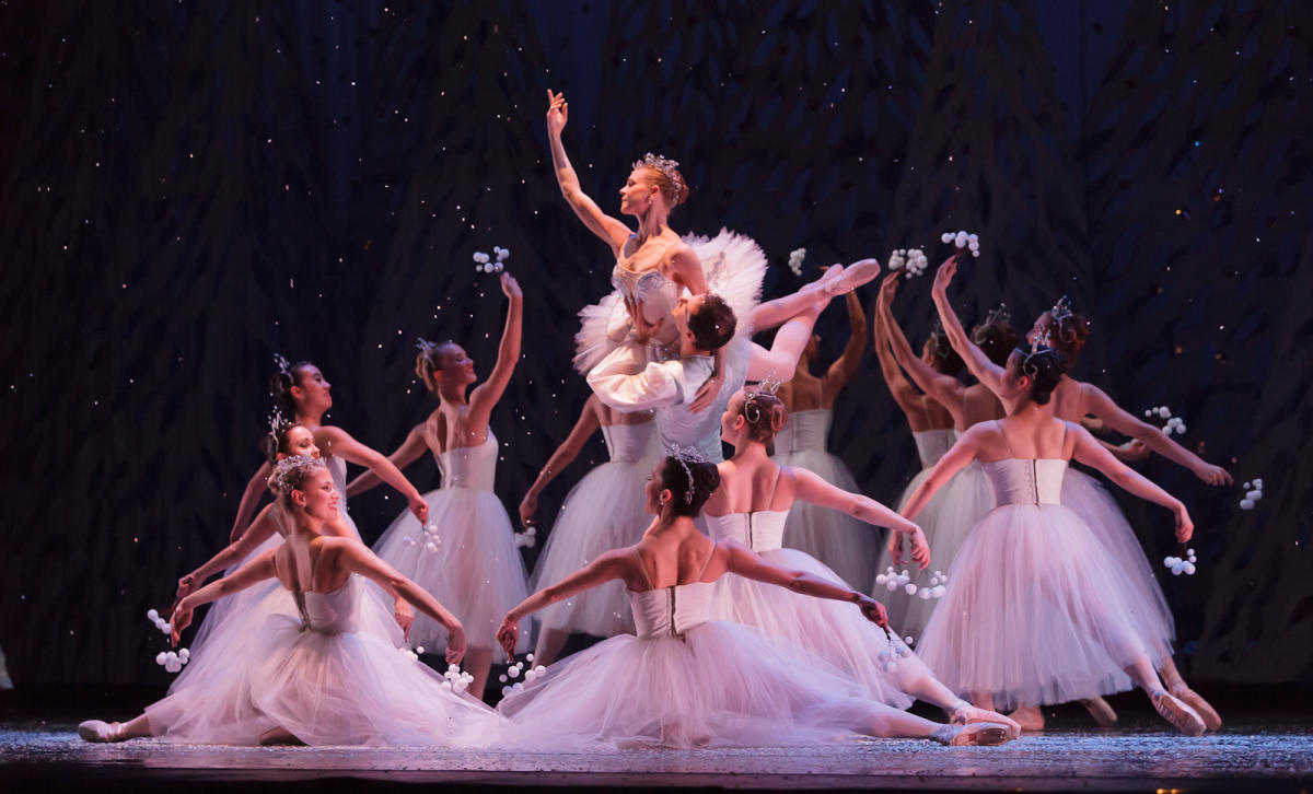 More than a dozen women dressed in white surround the Sugar Plum Fairy, also dressed in white, whose held in the air by a man in white in the center of the circle.