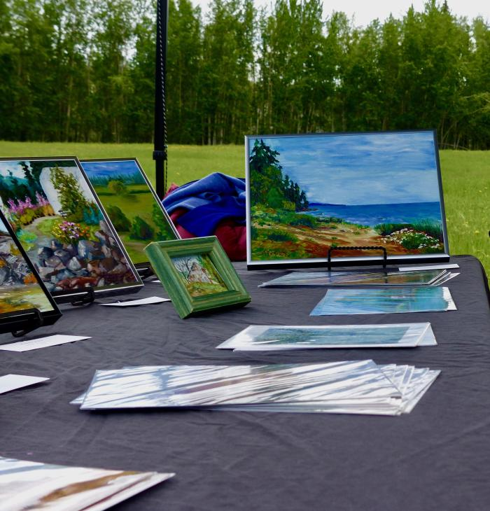 Landscape paintings on an event table in a green park