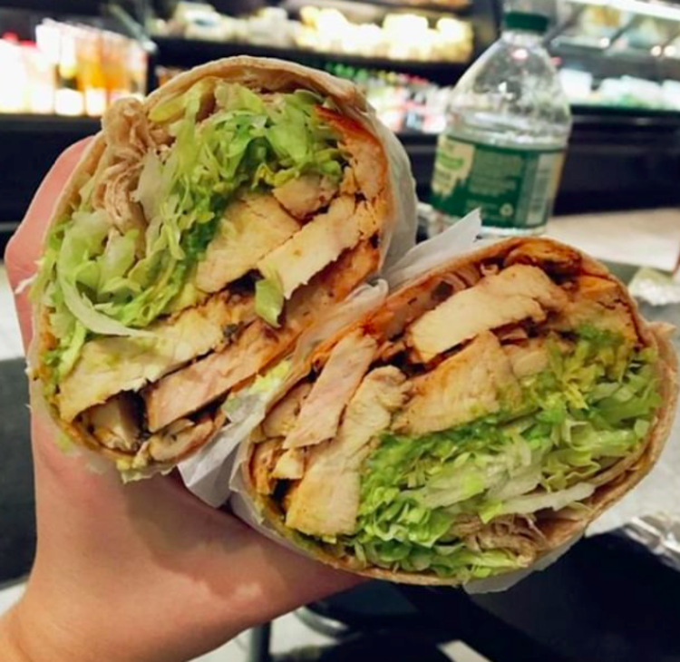 A lunch wrap is being held up filled with lettuce, chicken, avocado and more.
