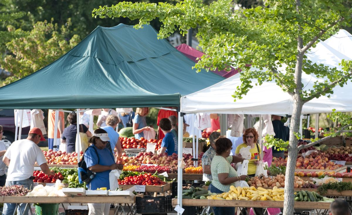 people shopping for fruits and vegetables under tents at a farmers market