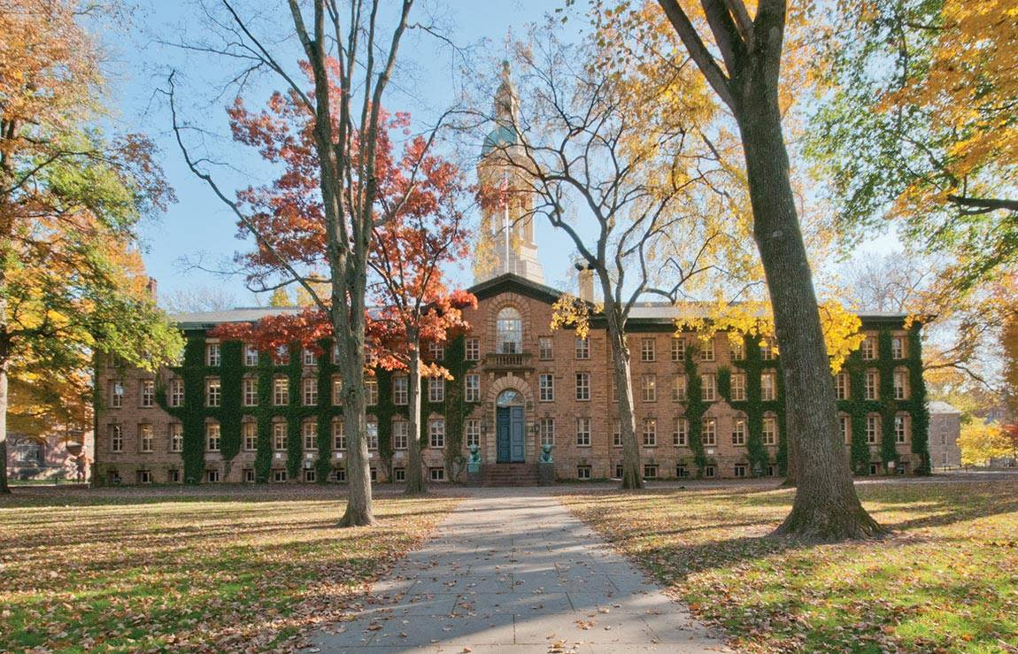 Outside view of Princeton University clock tower building between the fall trees