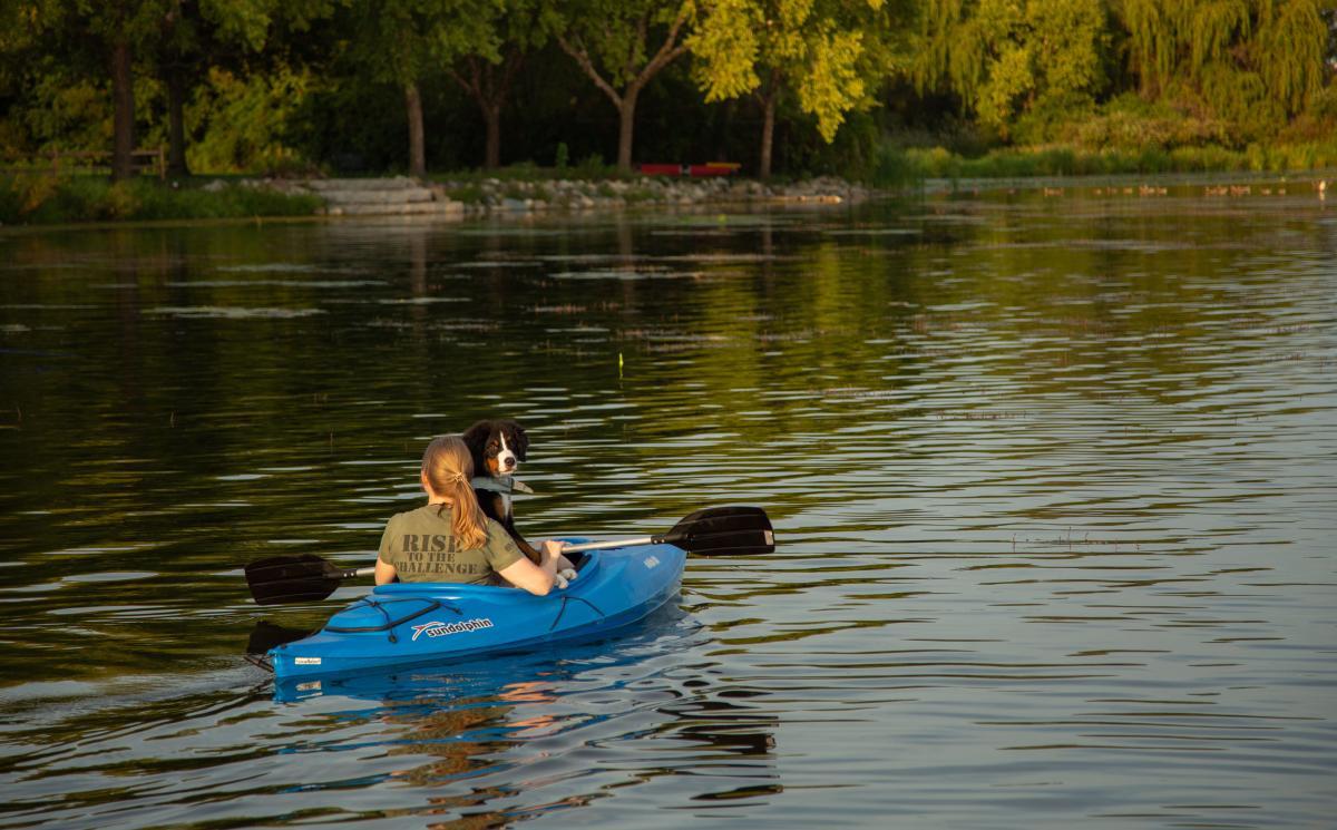 Woman and dog kayaking on Lake Wingra in Madison, WI