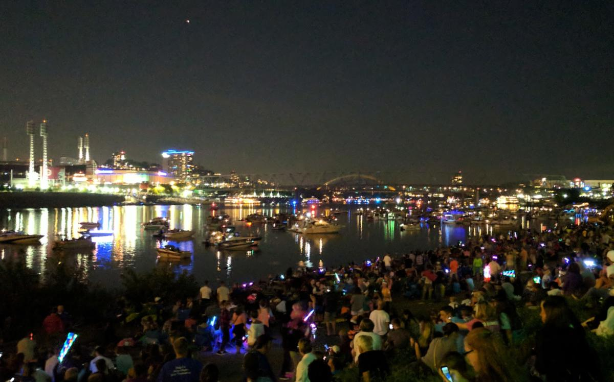 A crowd of people in the dark, sitting on the banks of the Ohio river at Riverfest