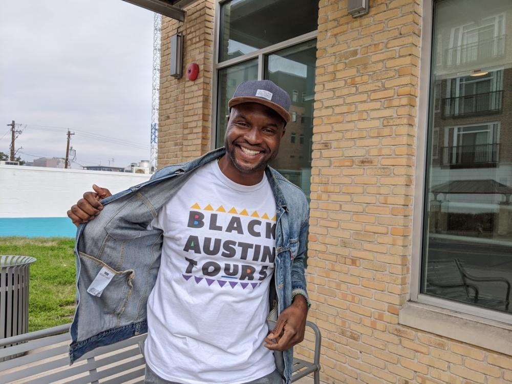 Black Austin Tours Guide and Founder Javier Wallace wearing logo shirt in Austin Texas