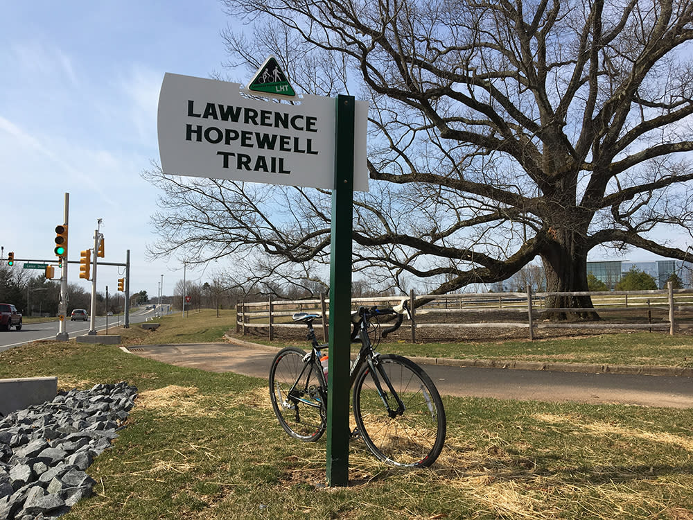 A bike parked at the sign for the Lawrence Hopewell Trail