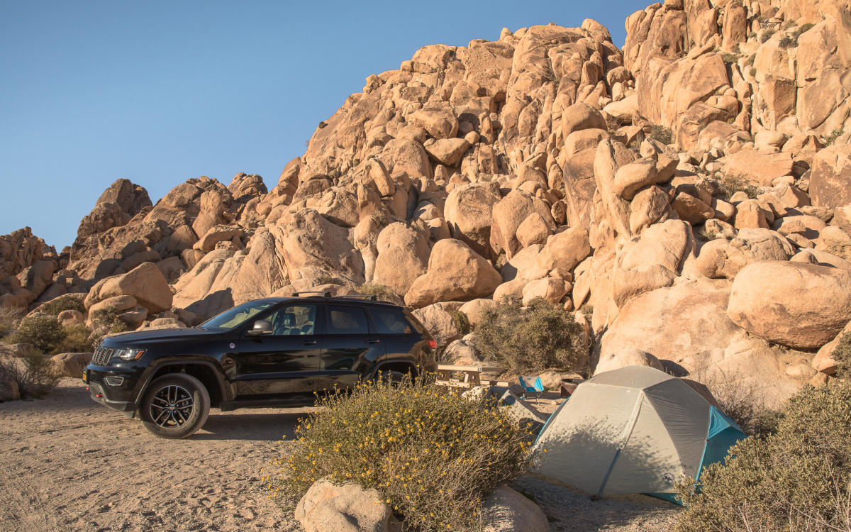Car and tent at campsite in Indian Cove Campground in Joshua Tree National Park