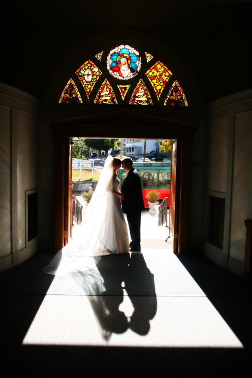Bride & Groom under a stained glass window