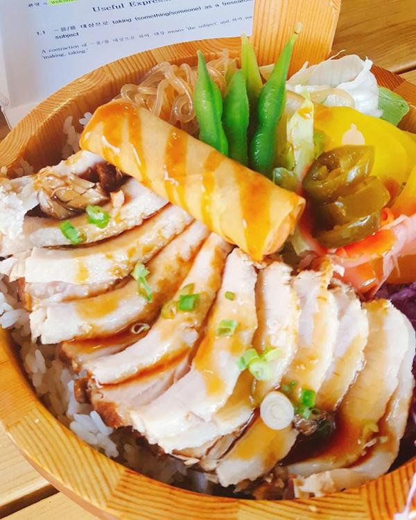 bowl of food with chicken, vegetables and an egg roll