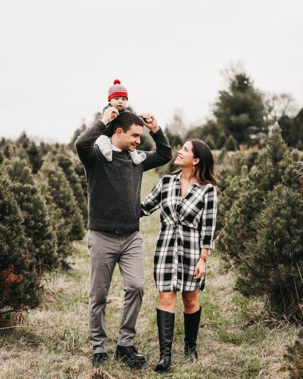 Young family strolls through holiday tree farm