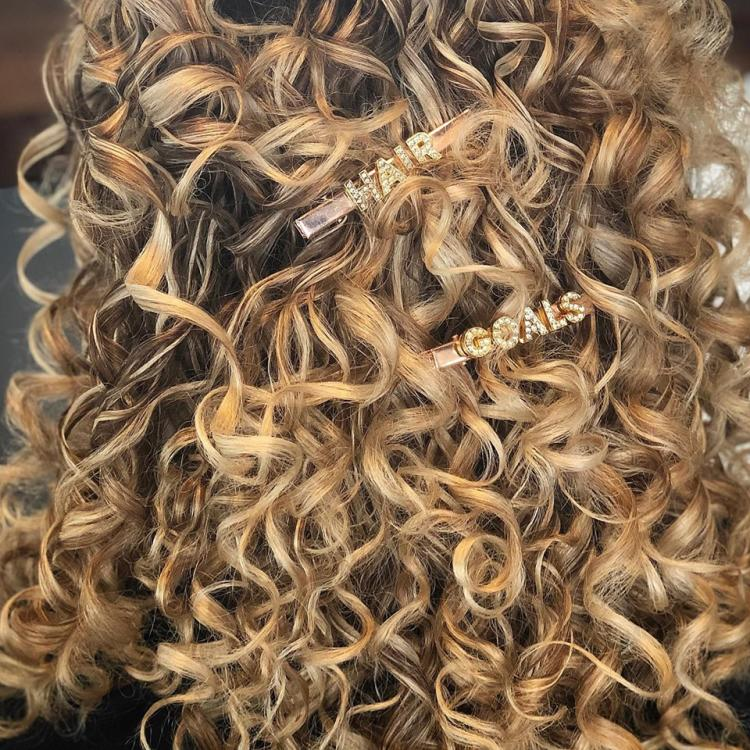 A head full of curls with pins reading Hair Goals