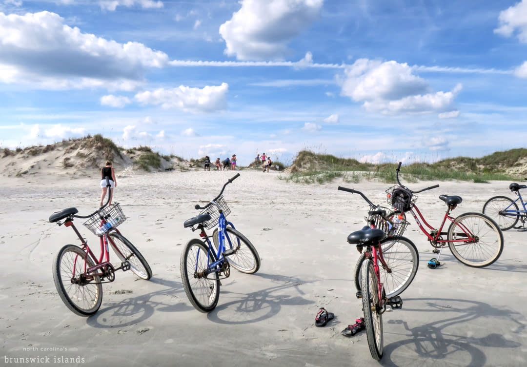 Bikes parked in the sand with people walking along the Brunswick Islands dunes