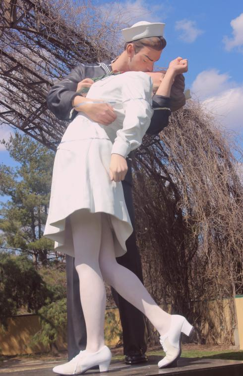 a larger than life sculpture of a sailor kissing a woman in a white dress