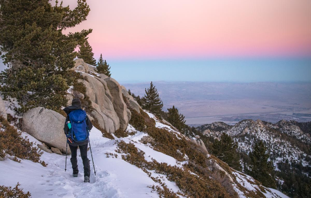 Woman hiking San Jacinto Peak in the snow at sunset