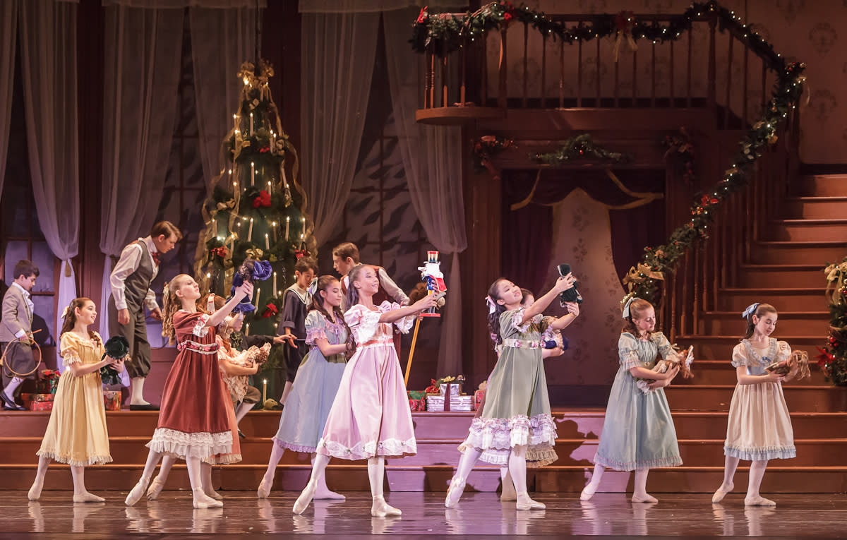 Young girls on stage holding dolls while young boys look at a Christmas tree in the background.