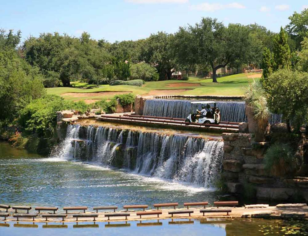 Golf kart crosses over waterfall and golfcourse at Horseshoe Bay Resort near austin texas