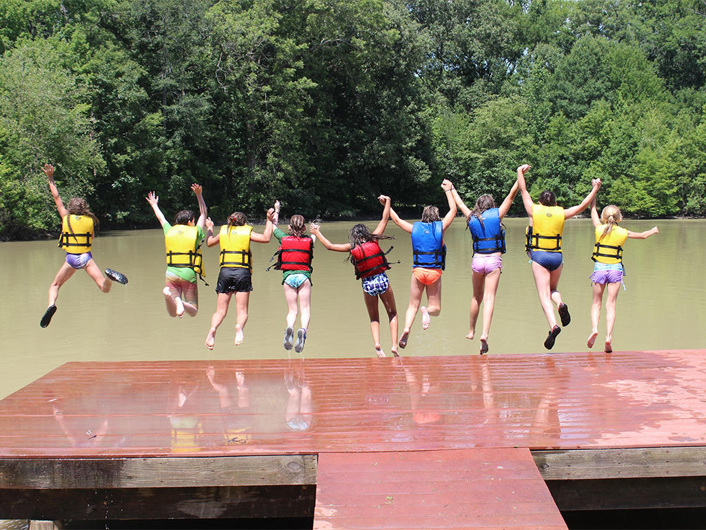 Howell Woods summer camp as kids jump off a dock into the river.