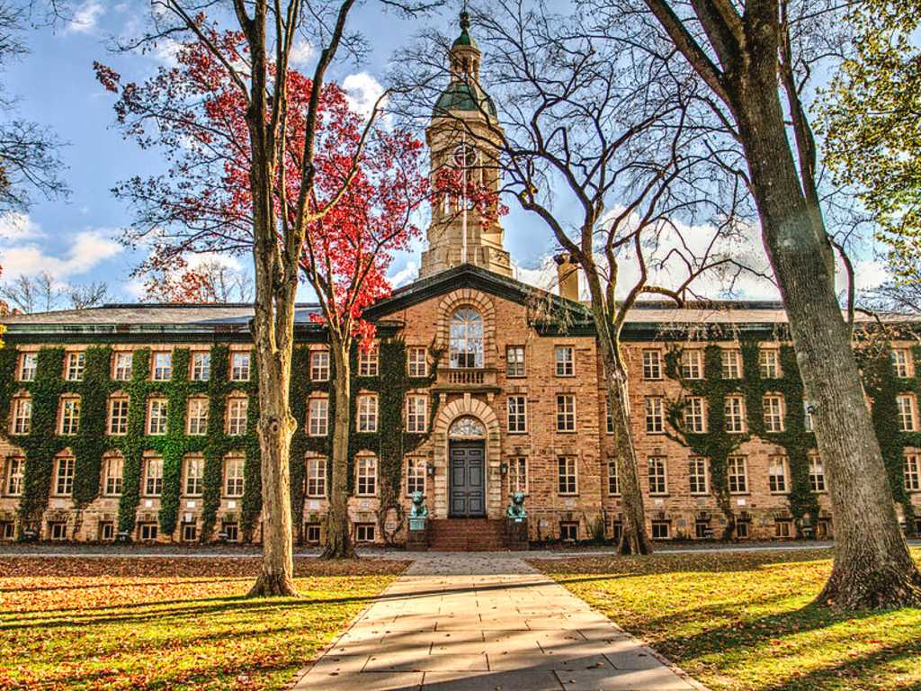 This is an image of the main building at Princeton University. It is a very large building, extremely wide and tall. The building also has many windows on it, with a very large set of double doors front and center.