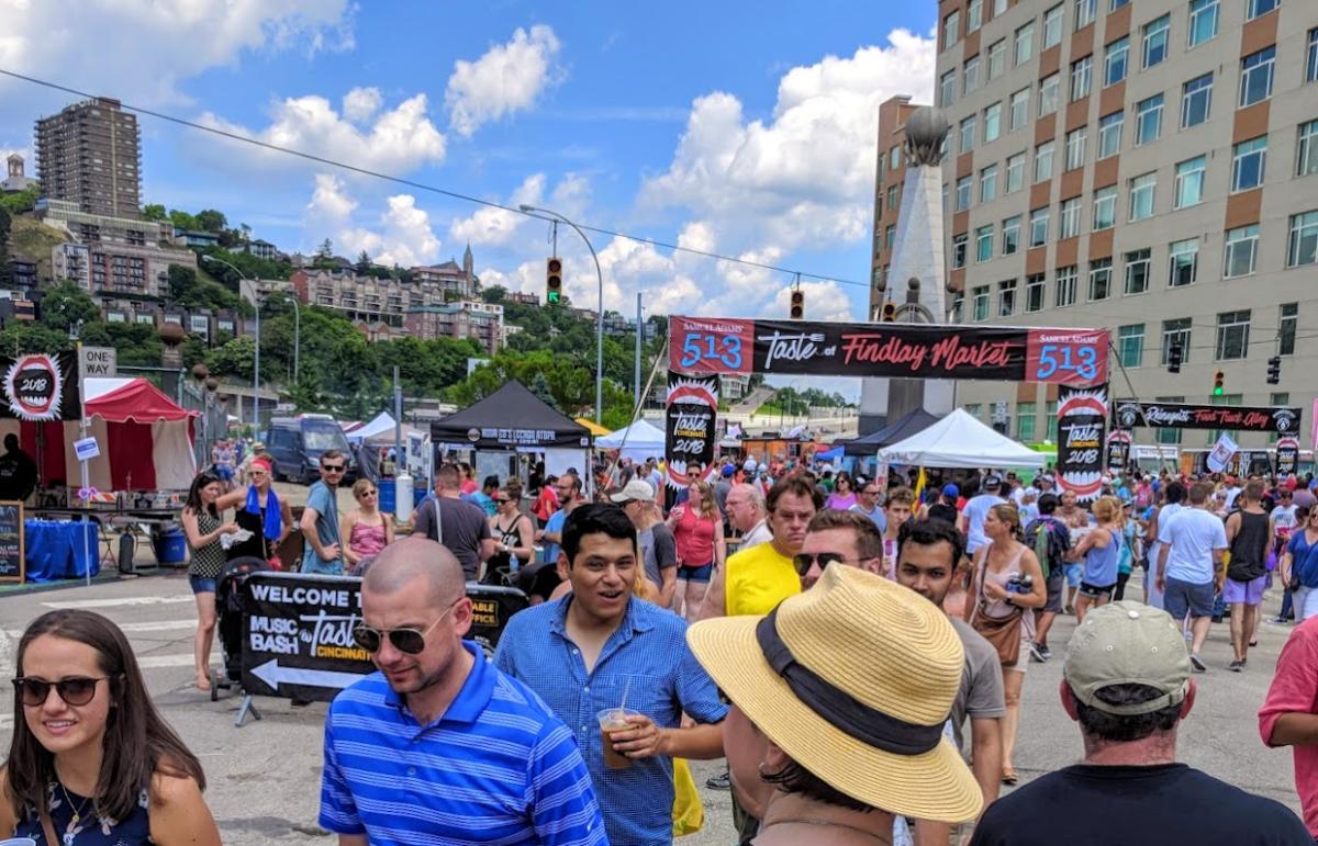 Taste of Cincinnati crowd in downtown Cincy headed under banner with blue sky and Mt. Adams in background